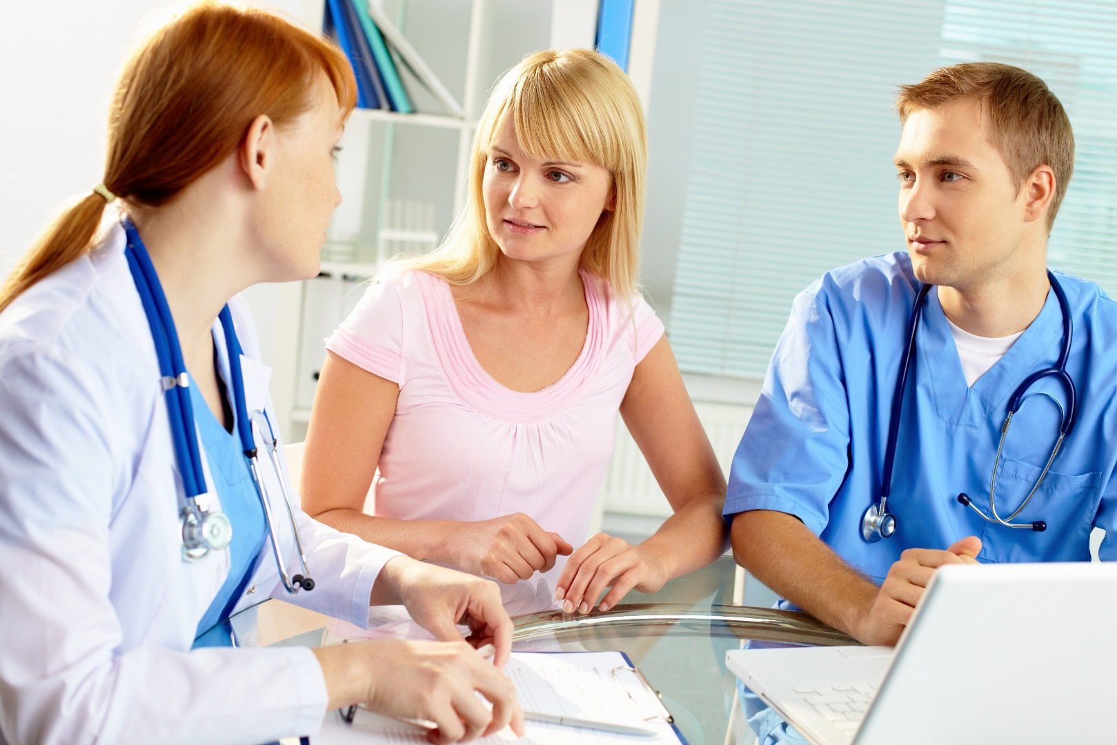 Portrait of confident practitioner consulting patient in hospital